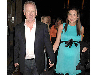 Les Dennis' fiancée shows baby bump at book launch