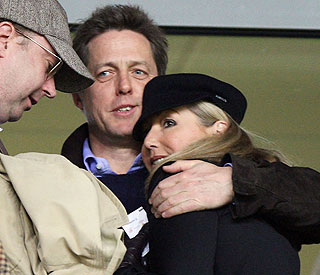 Hugh Grant cosies up to mystery lady friend at football