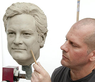 Final touches on King Colin Firth's waxwork
