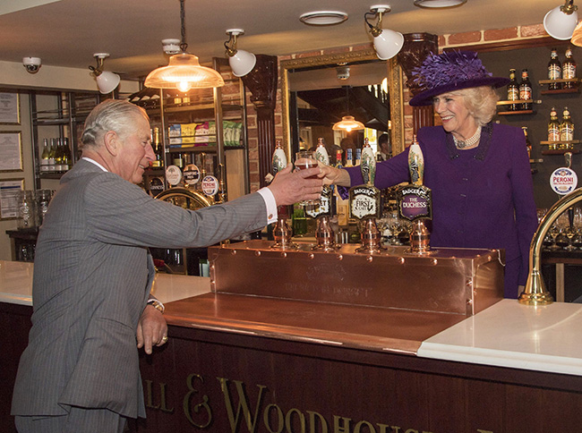 Camilla, Duchess of Cornwall pours pint for Prince Charles in pub in Poundbury
