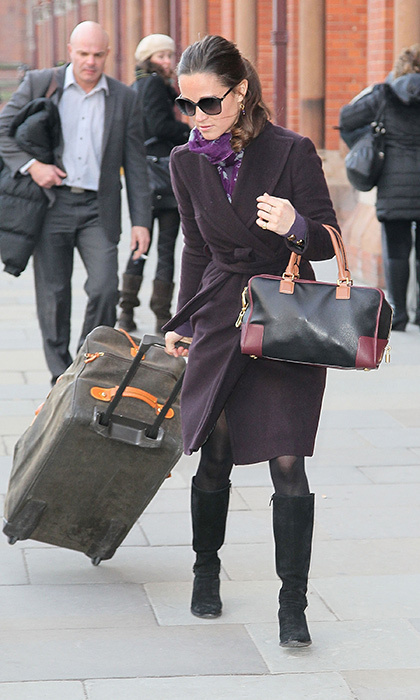 Even when toting heavy luggage, she managed to look flawless in a purple coat, matching scarf and oversized sunglasses.