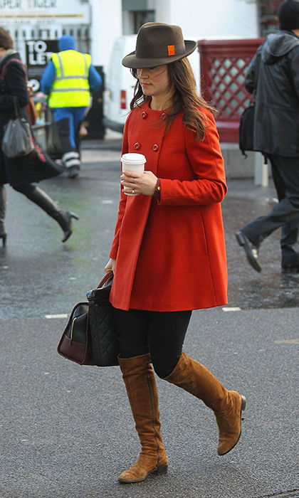 She perfected fall street style in this orange coat, brown suede boots and fedora.