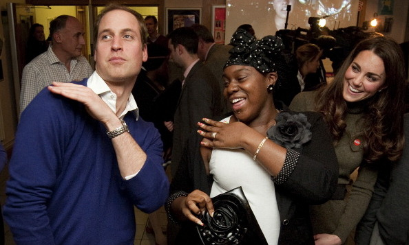 Prince William shows off his moves during a reception at Centrepoint's Camberwell Foyer in 2011 as his wife Kate looks on.