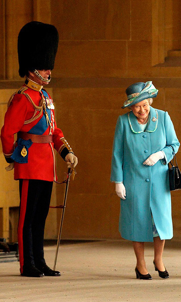 Queen Elizabeth ll gets a fit of the giggles as she walks past her husband, Prince Philip, Duke of Edinburgh, who is standing to attention in his uniform and bearskin hat at Buckingham Palace in 2003.