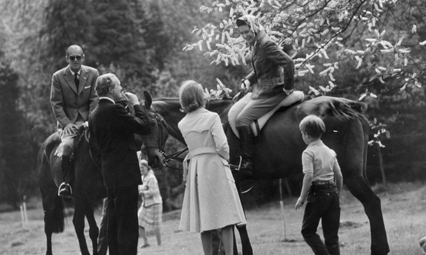 The Queen and Prince Philip stop for a chat while riding horseback in Windsor Great Park in 1971.