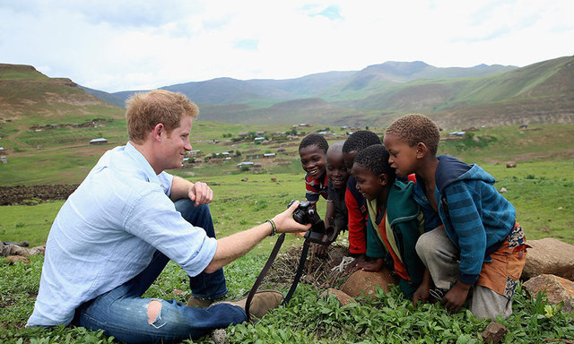 Prince Harry shows children a photograph he has taken during a visit to a herd boy night school constructed by Sentebale on December 8, 2014 in Mokhotlong, Lesotho.