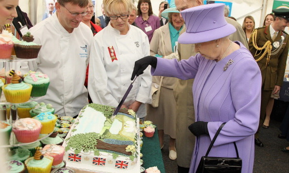 The Queen, looked like a confection herself in cheery lilac, knighted a special Jubilee cake in her honor during a country-wide Diamond Jubilee Tour circa May 2012.