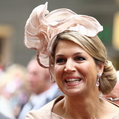 The royal was all smiles in a champagne chiffon cocktail hat upon her arrival at Haus der Niederlande in Muenster, Germany.