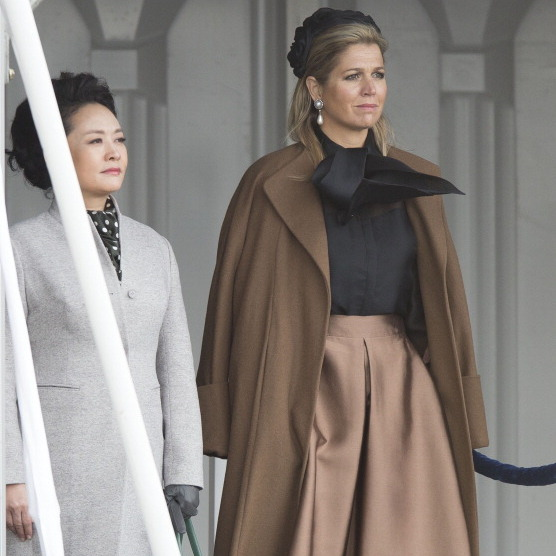 Listening to the national anthem upon the arrival of Chinese President Xi Jinping at Schiphol International Airport, the royal wore a demure noir rose hat.