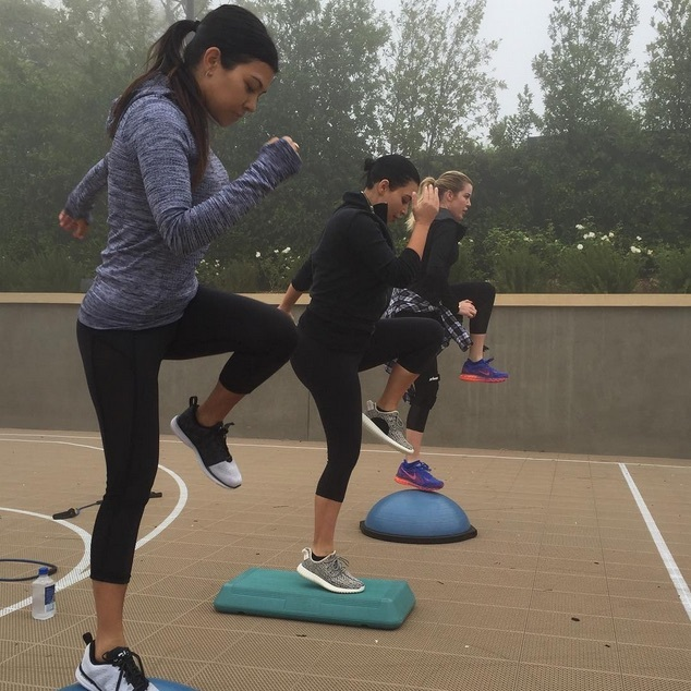 "Kourtney Kardashian got some family bonding in by working out in the rain with her sisters Kim and Khloe in Michi's ""Stardust"" crop pant. 