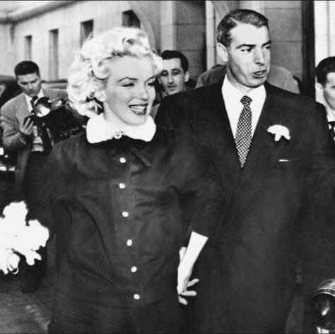 Playing the role of demure wife, Marilyn chose a simple black suit with white mink trim for her surprise wedding in 1954 to Yankee baseball player Joe DiMaggio.