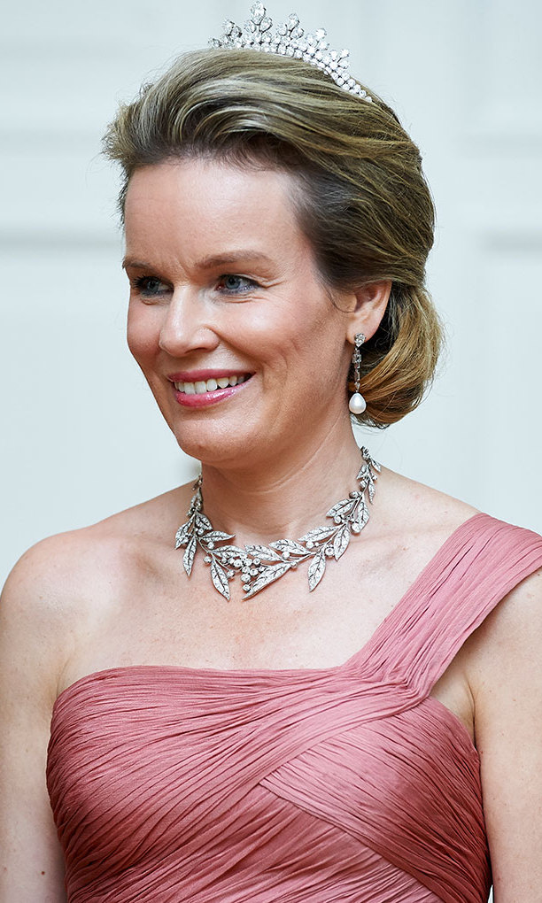 Queen Mathilde of Belgium dazzled in a dusky pink dress and beautiful diamond-encrusted jewellery - including the famous Wolfers tiara that belonged to Queen Fabiola - at an official dinner in Warsaw, Poland during her and King Philippe's tour there.