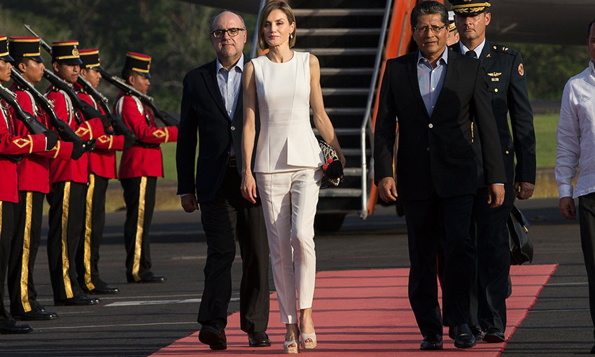 Arriving in Honduras, the Queen's white pants and wedges look was given a sophisticated twist with a fitted sleeveless top.