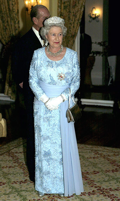 The Queen attended the second day of her official tour of Jamaica in 2002 wearing a blue embroidered dress with silk sash.