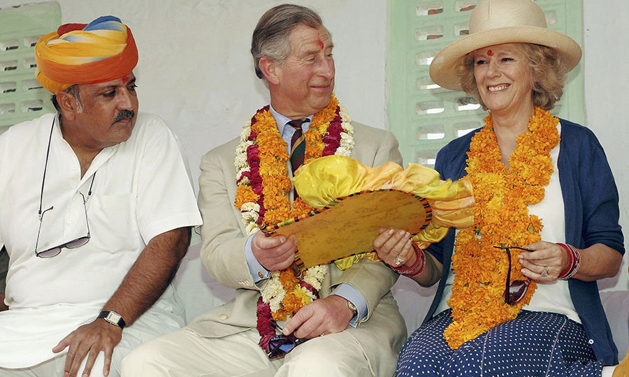 Prince Charles handed a fan to his wife Camilla, Duchess of Cornwall during their visit to Artiya Village on March 29, 2006.