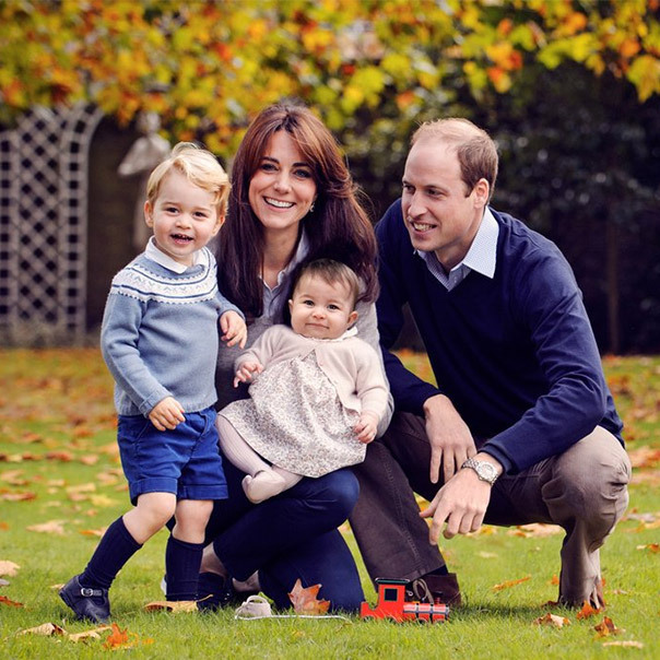 Princess Charlotte smiles while balancing on mom Kate's knee in the family's first official portrait as a foursome. 