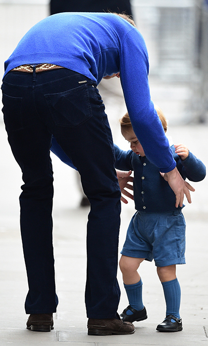 Overwhelmed by the crowds and camera flashes outside the Lindo Wing, Prince George looked for the comfort of his father's embrace.