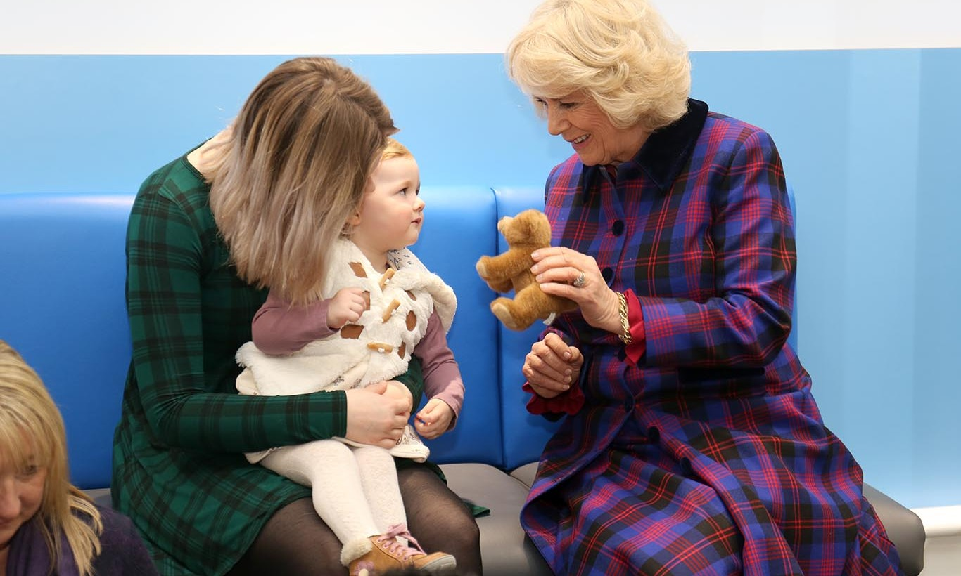 Duchess Camila meets a new friend, 21-month-old Kyla Bailey-Webb, at Boots Opticians in the United Kingdom. 