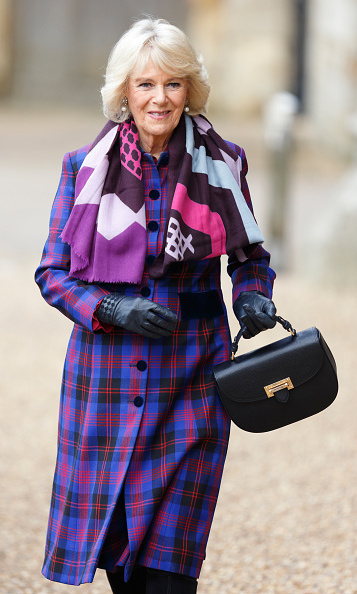 Camilla, Duchess of Cornwall shows that mixing motifs can be both fun and classic, with a tartan coat and purple print scarf anchored by a classic black handbag and leather gloves. 