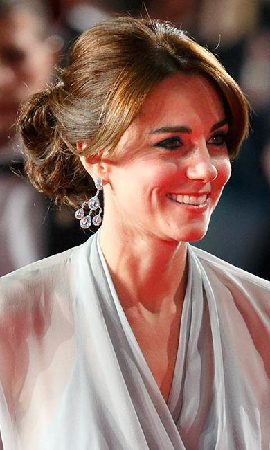 Kate could have passed for a Bond girl with her glamorous updo from the <i>Spectre</i> premiere. To re-create this look, divide your bangs into two sections, top and bottom, and part them down the middle. Brush the bottom sections into your updo, but leave the top sections loose for an effortless finish. For the updo, choose what is most comfortable for you, such as a bun or chignon.