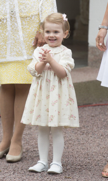 July 2014: Celebrating her mommy! Estelle couldn't help but smile during Crown Princess Victoria's 37th birthday party. 
