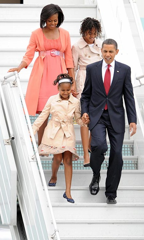 July 2009: Little ladies of fashion! Sasha and Malia were escorted by their parents in style as they wore neutral colored trench coats during a trip to Moscow.