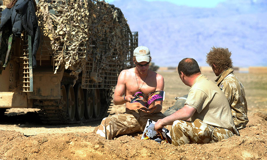 A shirtless Prince Harry read a magazine near his Spartan armored vehicle in the desert on February 19, 2008 in Helmand Province, Afghanistan. 