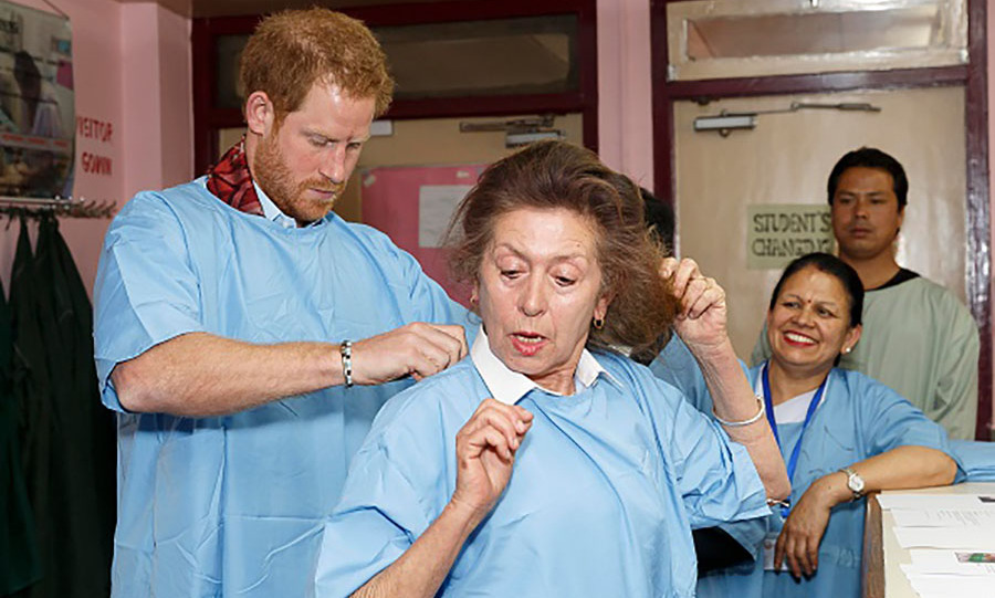 Prince Harry helped a staff member at the Kanti Children's Hospital suit up before visiting young burn victims. 