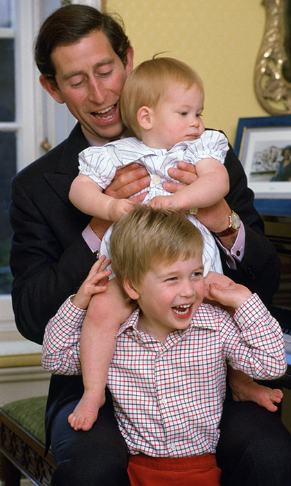 Little Harry climbs on his older brother's shoulders with the help of their father Charles. 
