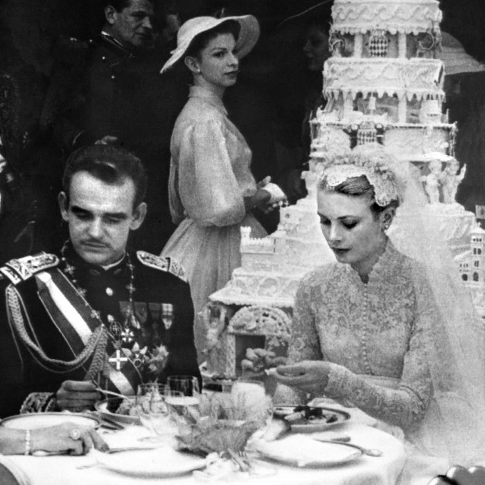The newlyweds sit in front of their massive six-tier wedding cake, which they cut using the Prince's sword.