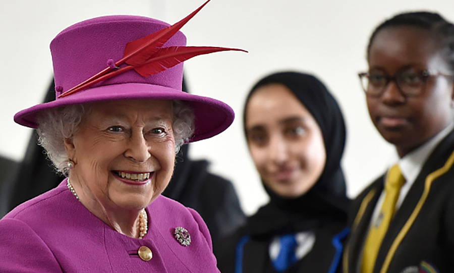 Queen Elizabeth wore a fuchsia hat with red feather detail during her visit to the Lister Community School in Plaistow.