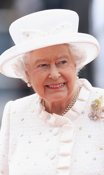 All white with a bow to match! Queen Elizabeth wore a white topper complete with a small bow during a visit to the Technical University.