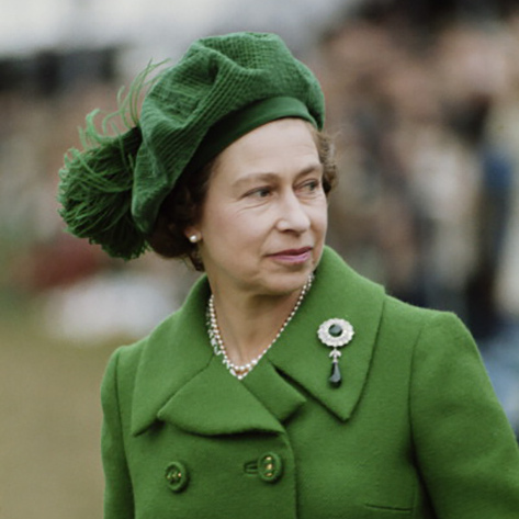 A beret style in green matched her emerald brooch in this vintage shot.