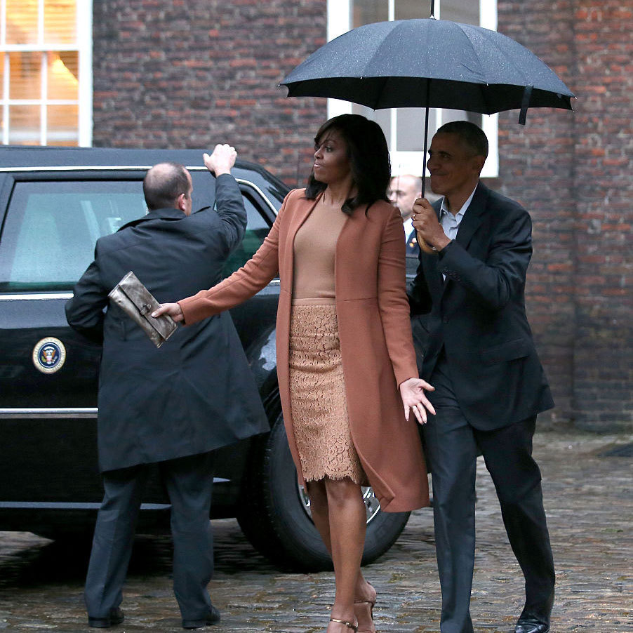"A little rain didn't bother the first lady as she exited her car at Kensington Palace. In fact, earlier in the day, President Obama said during a press conference with Prime Minister David Cameron that he ""warmed up"" for important meetings Friday morning by playing a couple classic Prince songs including <i>Purple Rain</i>.
