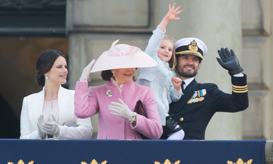 Hold on to your hats! In the arms of her uncle Prince Carl-Philip, little Princess Estelle of Sweden shows her enthusiasm alongside grandmother Queen Silvia, in pink, and aunt Princess Sofia. 