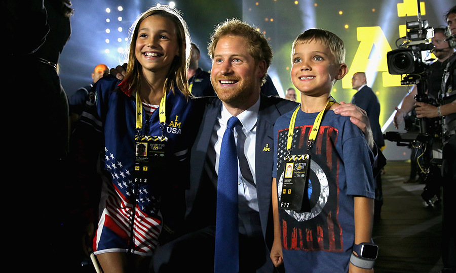 Harry couldn't help but smile as he posed for a picture with children of servicemen and women during the opening ceremony of the Invictus Games. 