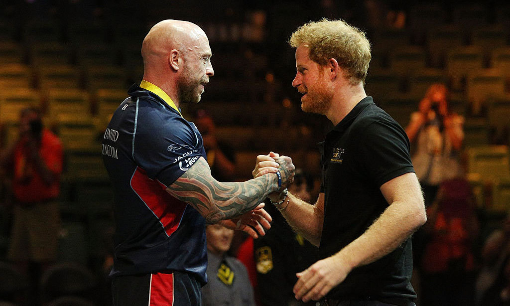 "Looks like Harry is power lifter Michael Yule's good luck charm! The Team U.K. competitor took home the gold for his 418.9 lb lift. As he made the impressive hoist, the royal shouted, ""Come on, Micky!"" Following the competition, the two embraced each other with a handshake at the medal ceremony.