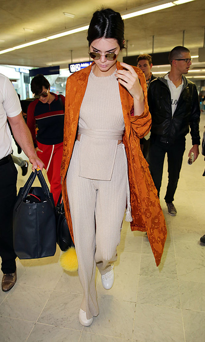 May 11: Kendall Jenner turned the Nice airport into her own personal runway upon her arrival in Cannes. The model strolled through the French airport rocking a neutral ensemble that she topped off with an orange coat.