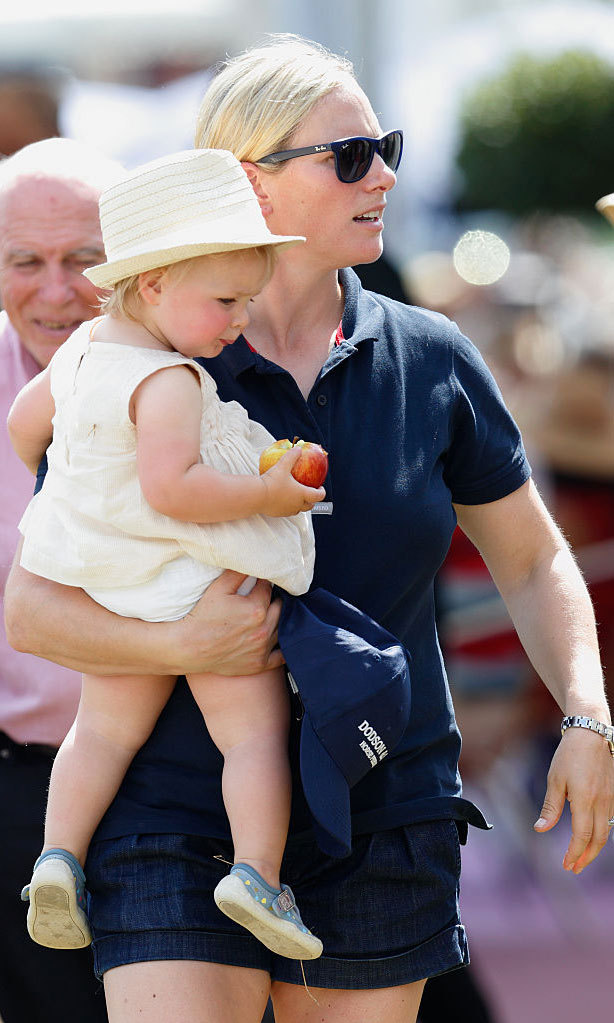 Festival fun! Zara Phillips carried her precious, apple-snacking little girl during the Festival of British Eventing at Gatcombe Park in 2015 in Stroud, England.