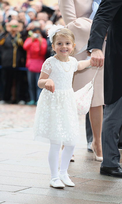 Isn't she adorable! Prince Oscar's older sister Princess Estelle looked angelic in a white flower patterned dress, white tights and little Mary Janes. She added a large floral hairpiece to complete her outfit.