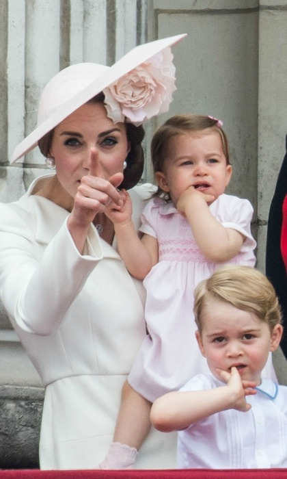 The Duchess directed her young children's attention as the royal family gathered on the balcony of Buckingham Palace to watch the Royal Air Force flyover.