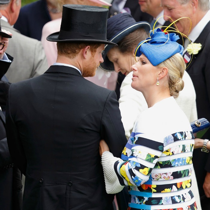 Zara Phillips hung on to cousin Prince Harry during the first day of the races.