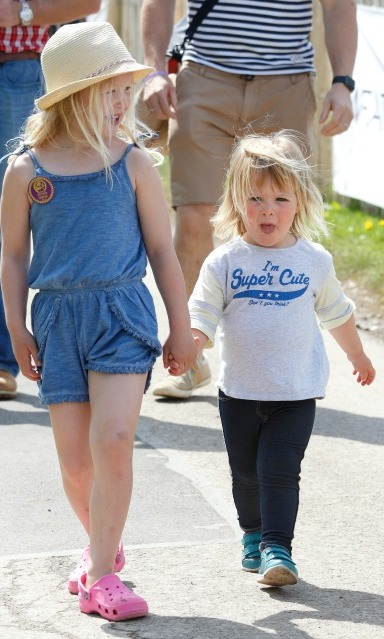 "Looking adorable in a shirt that read ""I'm super cute"" while walking hand-in-hand with her older cousin Savannah Phillips during the Badminton Horse Trials.