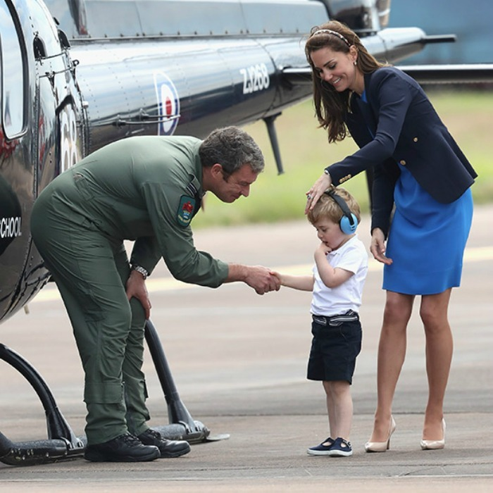 The stylish royal brushed her son's hair as he shyly greeted a pilot on the tarmac.
