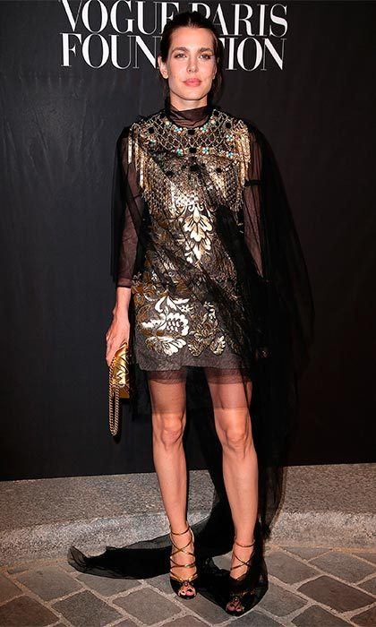 Embracing her darker side in this gold and sheer black gothic-style dress.