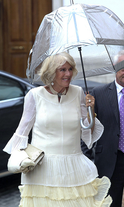 Among the guests was family friend Camilla, Duchess of Cornwall, who sheltered under an umbrella on her way into the church while wearing a frilled white dress and pearl necklace.