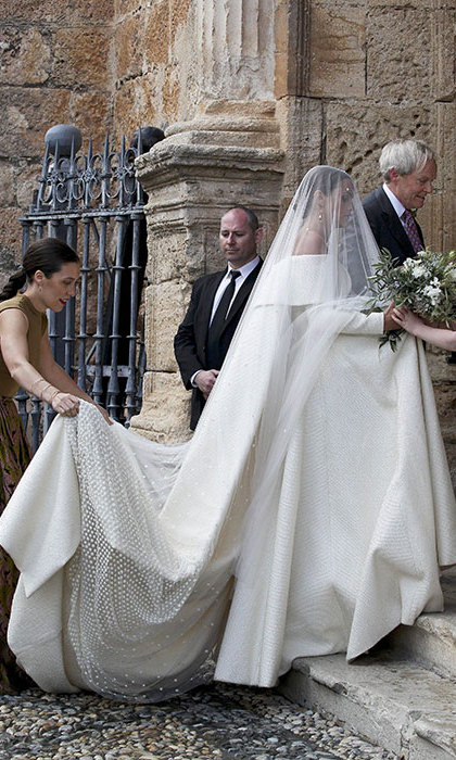 The bride wore a stunning off-the-shoulder, long sleeved wedding gown designed by Emilia Wickstead, which she accessorized with an elaborate dotted veil.
