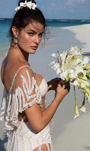 The 33-year-old rocked a totally sheer bridal gown by Brazilian label Agua de Coco over a white bikini.