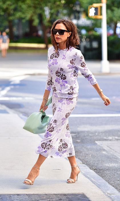 Victoria Beckham brightened the streets of New York City wearing a purple printed floral outfit paired with a mint green purse.