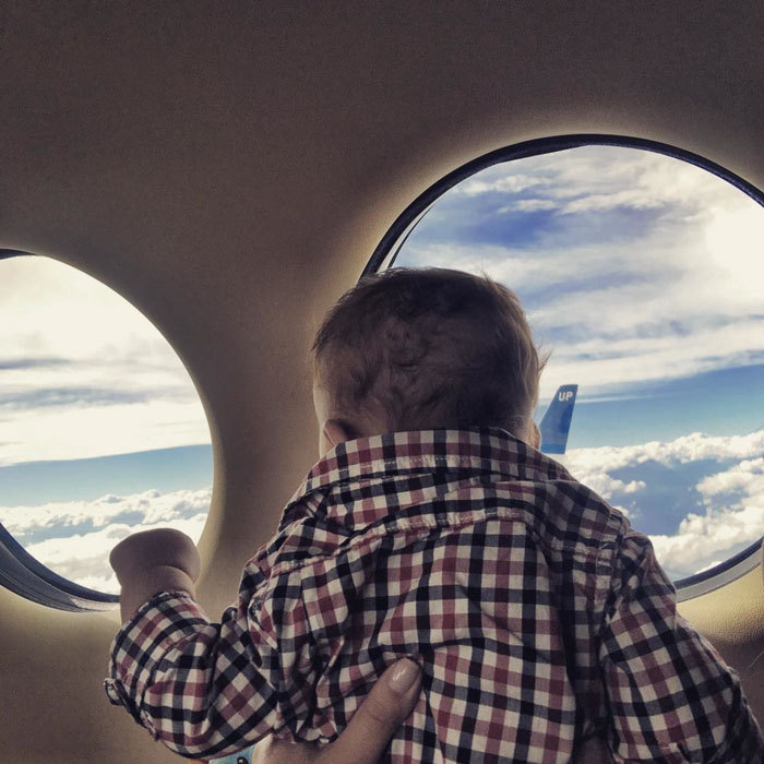 Up, up and away! Michael Phelps' son gazed outside the window of an aircraft during a flight with his family.
